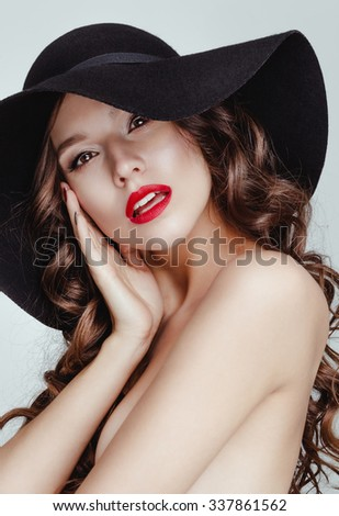 Sensual attractive charming brunette woman wearing a black hat posing in studio white background. Nude makeup with red lips and red nails. - stock photo
