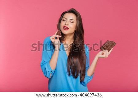 Sensual attractive young woman eating chocolate over pink background - stock photo
