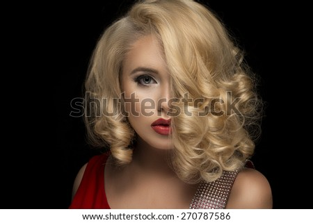 Sensual beautiful blonde woman posing. Girl with long curly hair.