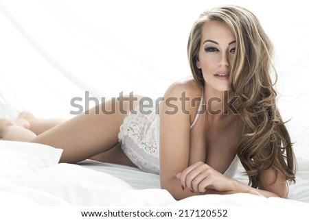 Sensual beautiful blonde woman posing in elegant lingerie in bed. Girl looking at camera.  - stock photo