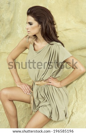 Sensual beautiful brunette woman posing in fashionable dress over stones, looking away. Summer photo. - stock photo