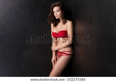 Sensual beautiful brunette woman posing in white lingerie. Girl with long curly hair. Studio shot. Glamour makeup. - stock photo