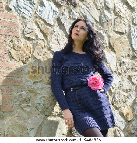 Sensual beautiful girl with rose in waiting pose looks up  near rough stone wall