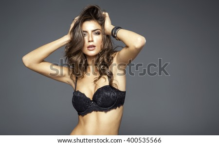 Sensual beautiful woman in lingerie posing. Girl with long curly hair - stock photo