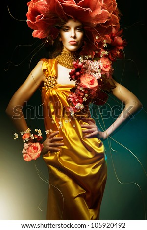 sensual beautiful woman in long yellow dress and flowers - stock photo