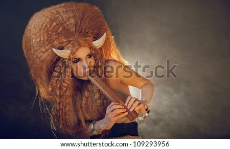 Sensual black eyed demon playing flute, real contact lenses - stock photo
