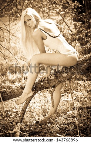 Sensual blond fashion model sitting on the tree