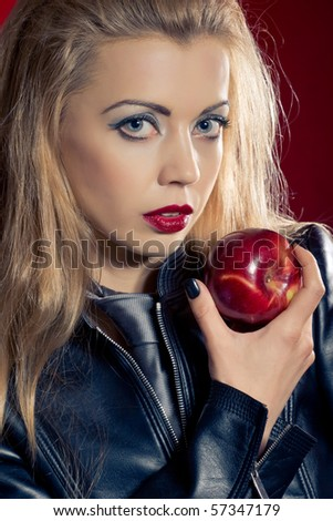 Sensual blond girl wearing a leather jacket offering an apple - stock photo