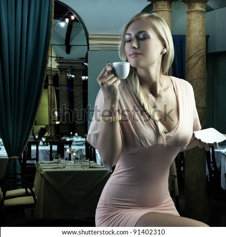 sensual blond girl with hair style drinking a cup of coffee in elegant pink dress over dark fashion background