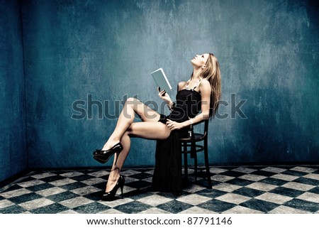 sensual blond in black dress and high heels sit on chair holding a book in empty room - stock photo