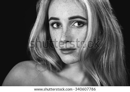 sensual blond woman with freckles portrait on black background, monochrome