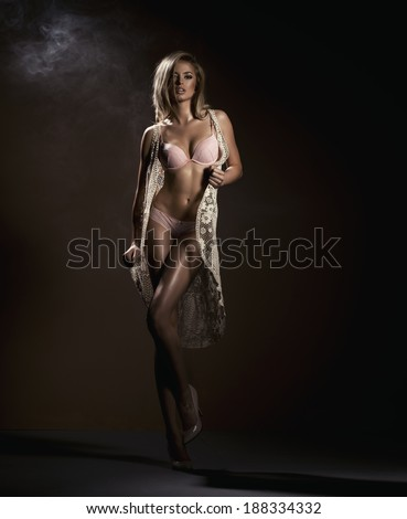 Sensual blonde woman posing in black sensual lingerie with toothy smile, looking at camera. Studio shot  - stock photo