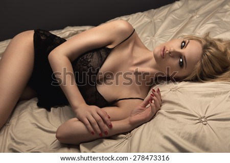 Sensual blonde woman posing in dark sexy lingerie on the bed - stock photo