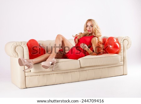 Sensual blonde woman posing over red hearts. Valentine's day. - stock photo