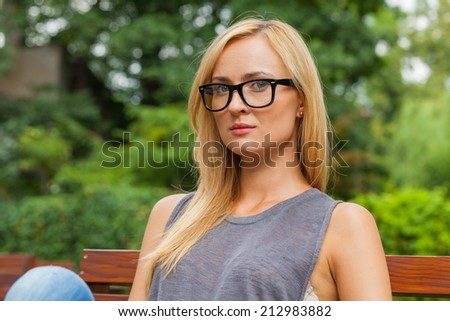 Sensual blonde woman sitting in park on wooden bench. Outdoor photo.