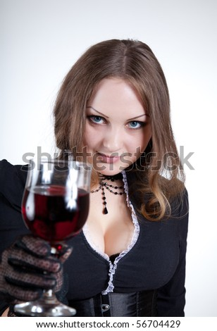 Sensual blue-eyed woman with glass of wine, studio shot