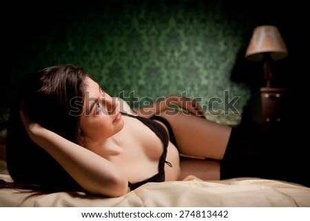 Sensual brunette in bed on green vintage background. Sexuality and sensuality. Boudoir and beauty - stock photo