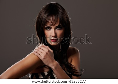 Sensual brunette lady portrait on grey background - stock photo
