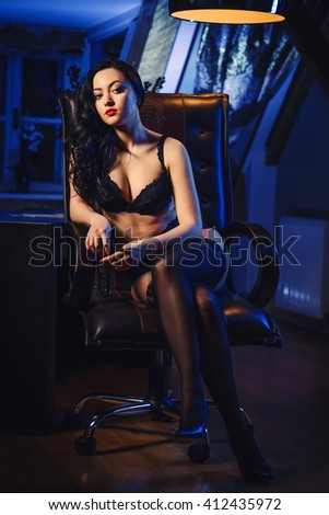 Sensual brunette with long hair posing in sexy lingerie and stockings indoors - stock photo