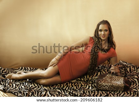 Sensual brunette woman in red dress reclining on an animal print rug, wearing a leopard print scarf and animal print handbag - stock photo