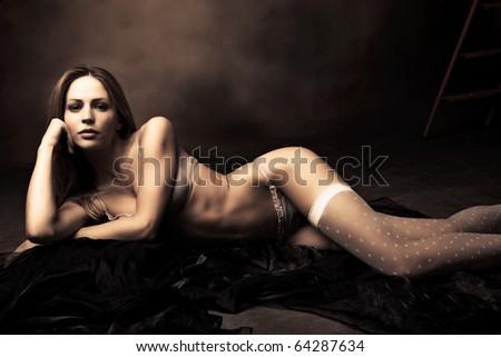 sensual brunette woman in underwear lie on floor posing, studio shot - stock photo