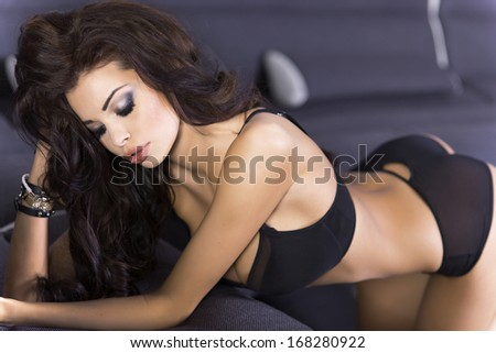 Sensual brunette woman posing in black sexy lingerie. - stock photo