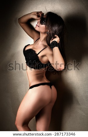 Sensual brunette woman posing in elegant black lingerie. Studio shot. Girl smiling.