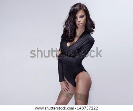 Sensual brunette woman posing, looking at camera.Long curly healthy hair. - stock photo