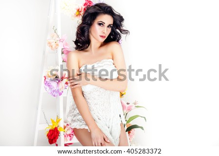 Sensual brunette woman posing with flowers, looking at camera. Studio shot.
