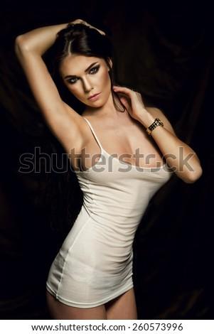 Sensual brunette woman posing with long wet hair. Studio shot. - stock photo