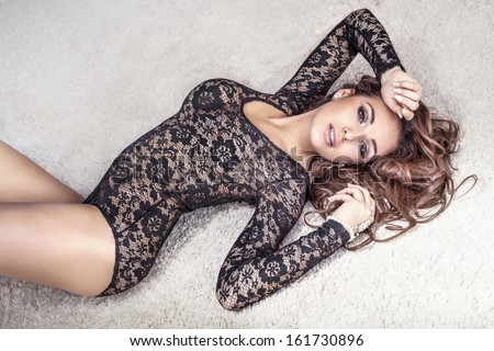 Sensual brunette woman with long hair lying on carpet in underwear, looking at camera. - stock photo