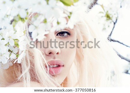 Sensual close up portrait of a spring woman, beautiful face female enjoying cherry blossom, dreamy girl with White fresh flowers outdoor, seasonal nature, tree branch and glamorous lady. - stock photo
