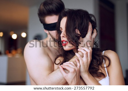 Sensual couple foreplay, milf with young lover, lace eye cover, bdsm - stock photo