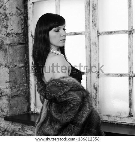 Sensual dark-haired woman in fur coat standing by the window, black and white portrait - stock photo