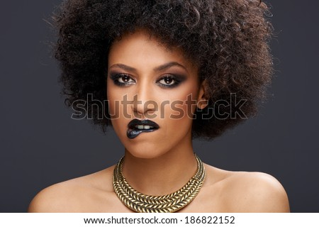 Sensual elegant African American woman with bare shoulders wearing a stylish gold choker and dark makeup looking at the camera biting her lip - stock photo