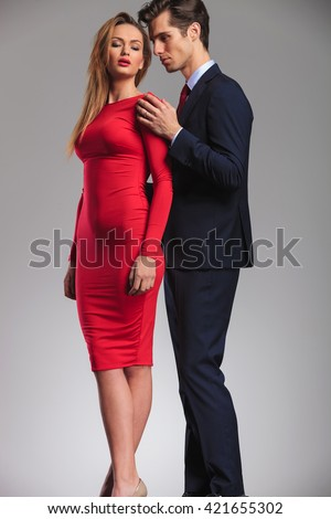 Sensual elegant couple standing embraced, man behind woman in red dress holding her close - stock photo