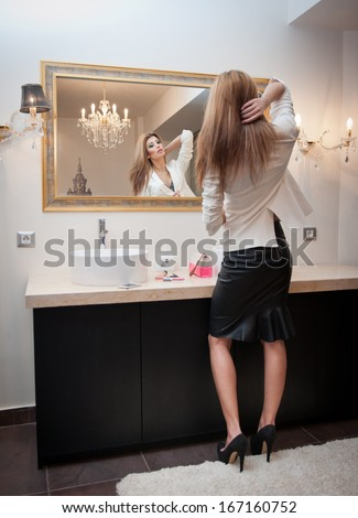 Sensual elegant woman in office outfit looking into a large mirror. Beautiful and sexy blonde young woman wearing an elegant white jacket and a black midi skirt posing in a mirror. Fashionable model. - stock photo