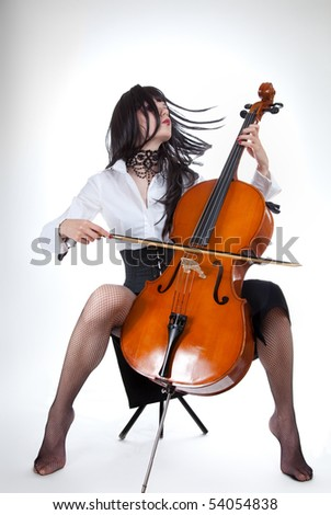Sensual girl playing cello and moving her hair, studio shot - stock photo