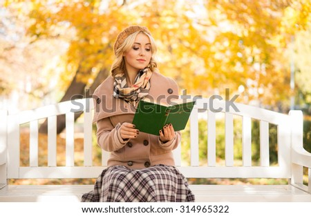Sensual girl reading a poetry book in the park sitting on the bench. - stock photo