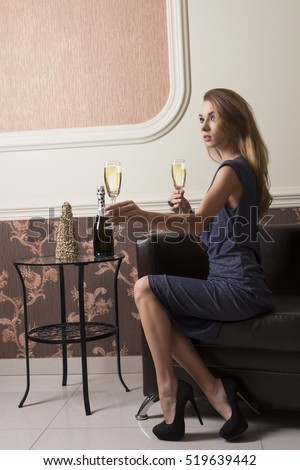 sensual girl with blue evening dress and heels is sitting on sofa in elegant ambient offering a flute of champagne. Chic party