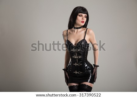 Sensual gothic woman wearing fetish latex outfit, miniskirt and stockings  - stock photo