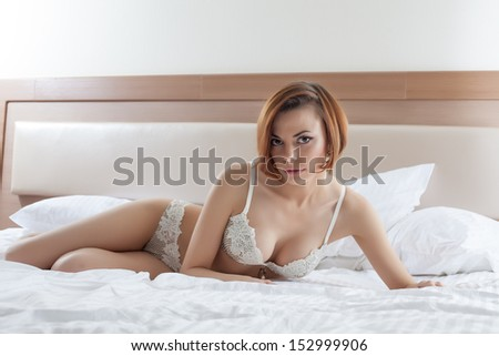 Sensual model posing in erotic lingerie on bed - stock photo