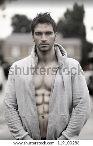 Sensual moody portrait of a great looking man in hooded jacket outdoors - stock photo