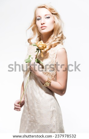 Sensual new year's eve fashion woman with blonde hair wearing gold dress. Holding a golden rose. Isolated against white. - stock photo