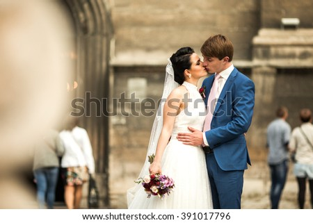 Sensual newlywed couple hugging & kissing near old church - stock photo