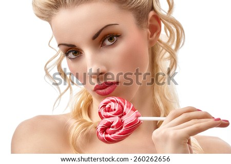 Sensual nude girl portrait with big lollipop in heart shaped. Perfect glowing skin, sexy lips. Gorgeous lady with brown eyes and blond hair. Beauty woman face closeup. Pin up styled - stock photo