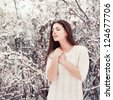 Sensual outdoor portrait of young beautiful brunette posing in snowy forest. - stock photo
