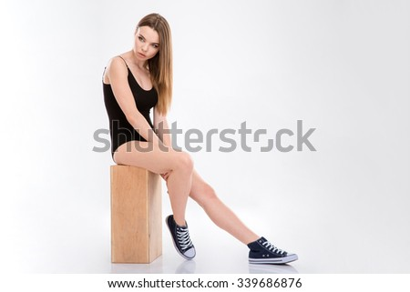Sensual pensive natural young woman in black swimsuit and sneackers sitting on wooden box  - stock photo