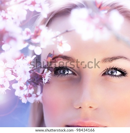 Sensual portrait of a spring woman, beautiful face, close up on blue eyes, female enjoying cherry blossom, dreamy girl with pink fresh flowers outdoor, seasonal nature, tree branch and natural beauty - stock photo