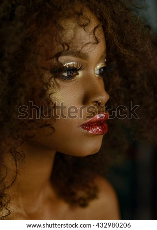 Sensual portrait of magic surreal golden african american female model with bright glitter makeup, glossy golden hairstyle and big red lips - stock photo